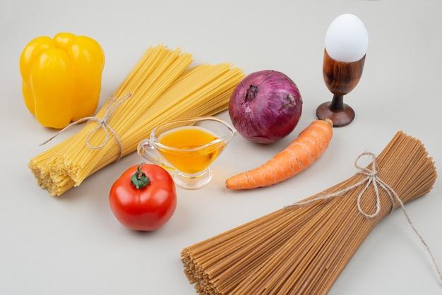 Ruwe deegwaren met groenten op witte achtergrond. hoge kwaliteit foto