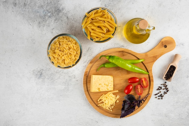 Ruwe deegwaren, olie, kaas en verse groenten op marmer.