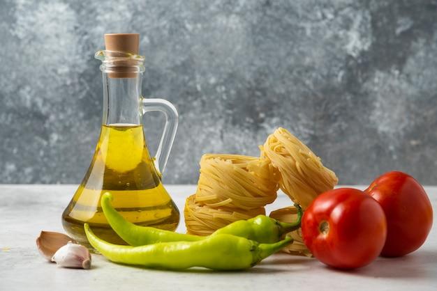 Ruwe deegwarennesten, fles olijfolie en groenten op witte lijst.