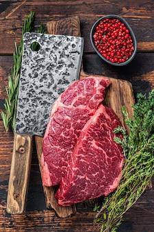 Ruwe denver sneed black angus biefstuk biefstuk op een slager bord met vlees hakmes.