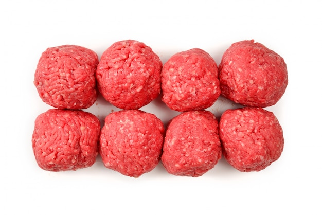 Ruwe die vleesballen op witte achtergrond worden geïsoleerd.
