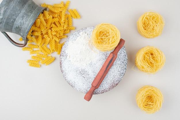 Ruwe diverse macaroni en bloem met deegroller op witte ondergrond