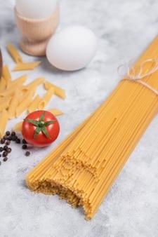 Ruwe droge spaghetti die met bruin bindgaren wordt gebonden dat op een marmeren achtergrond wordt geplaatst. hoge kwaliteit foto