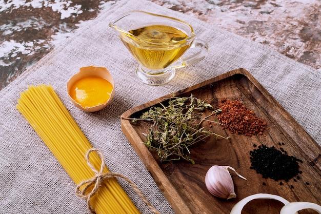 Ruwe droge spaghetti en gedroogde kruiden en eieren op bruin tafelkleed.