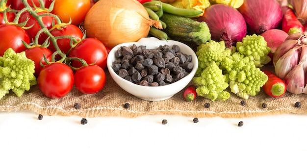 Ruwe droge zwarte kikkererwten en groenten die op witte dichte omhooggaand worden geïsoleerd