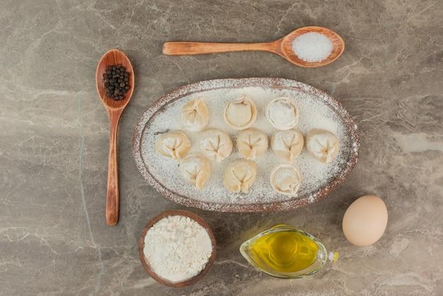 Ruwe dumplings met ei, olie, bloem en lepels.