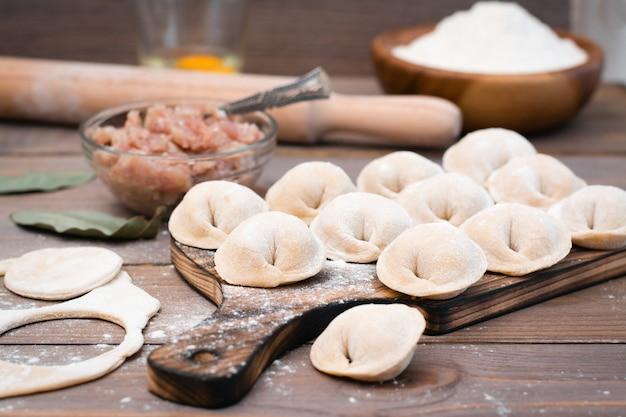 Ruwe dumplings op de snijplank en ingrediënten voor hun voorbereiding op een houten tafel
