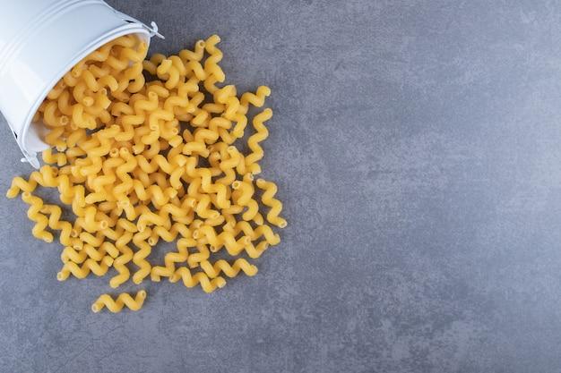 Ruwe elleboog macaroni uit metalen emmer.