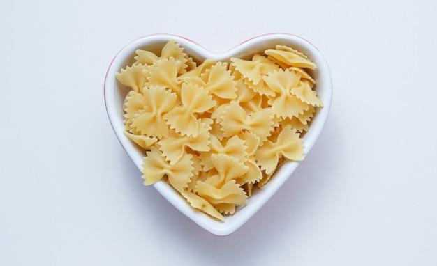 Ruwe farfalle pasta in een hartvormige kom op witte muur, bovenaanzicht.