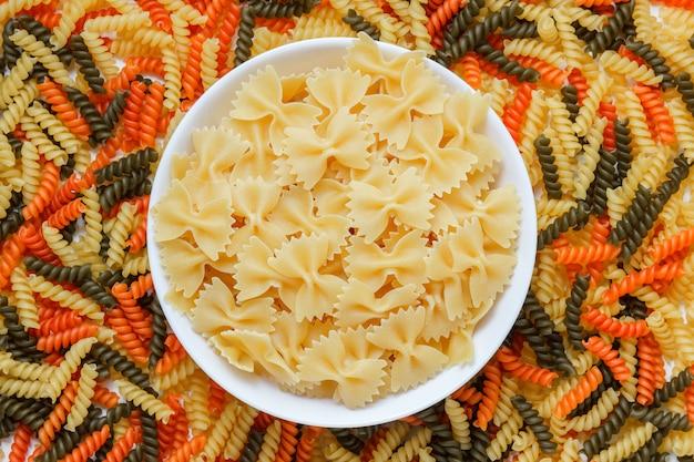 Ruwe farfalle pasta in een witte plaat plat lag op een gekleurde fusilli tafel