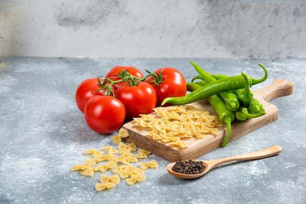 Ruwe farfalle, tomaten en chilipepers op een houten bord.