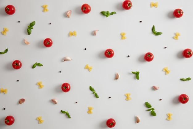 Ruwe farfalle vlinderdasvormige pasta, rode tomaten, basilicum en kruiden voor het bereiden van italiaans eten. selectieve aandacht. macaroni als bron van koolhydraten. traditionele keuken. verse, ongekookte ingrediënten