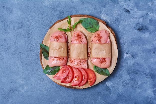 Ruwe filet met kruiden en specerijen op een houten bord op blauw