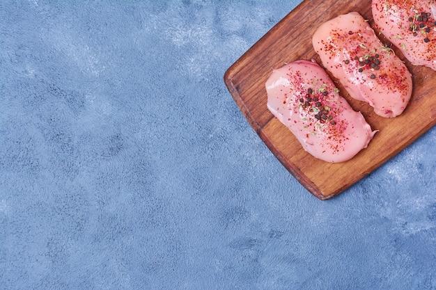 Ruwe filet met kruiden op een houten bord op blauw
