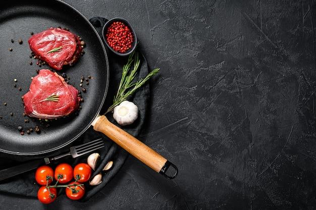 Ruwe filet mignon steak in een koekenpan. ossenhaas. zwarte achtergrond. bovenaanzicht. ruimte voor tekst