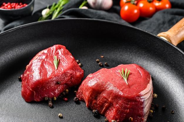 Ruwe filet mignon steak in een koekenpan. ossenhaas. zwarte achtergrond. bovenaanzicht