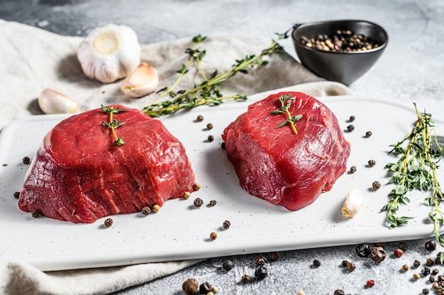 Ruwe filet mignon steak op een witte snijplank. ossenhaas. grijze achtergrond. bovenaanzicht