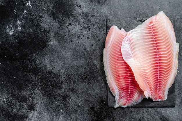 Ruwe filet van telapia op een snijplank. zwarte achtergrond. bovenaanzicht. kopieer ruimte
