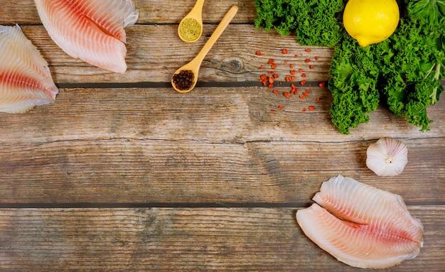 Ruwe filet van tilapia met specerijen en kruiden, citroen en knoflook, peterselie, boerenkool op rustieke achtergrond bovenaanzicht.