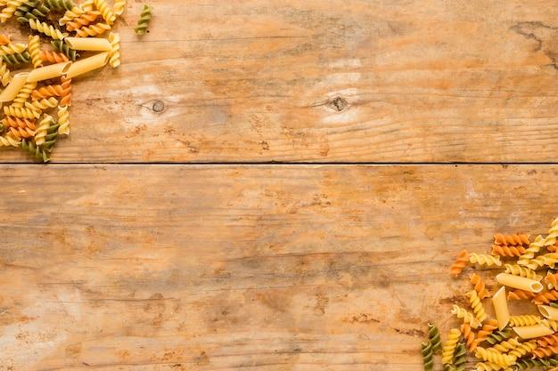 Ruwe fusilli en pennedeegwaren bij de hoek van houten achtergrond