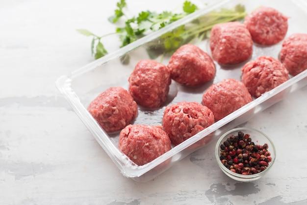 Ruwe gehaktballetjes met peper en zout in plastic doos