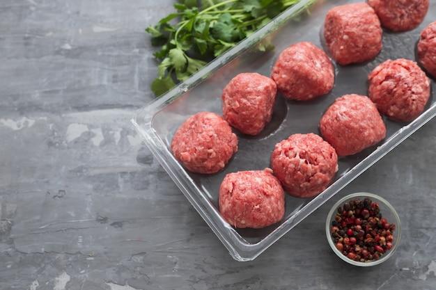 Ruwe gehaktballetjes met peper in plastic schotel