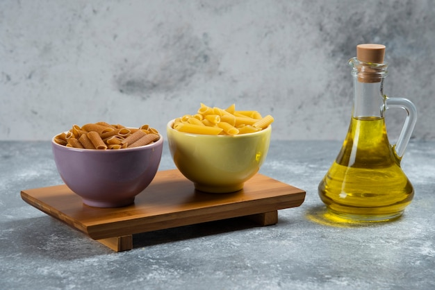 Ruwe gele en bruine griesmeeldeegwaren met een glasfles olie.