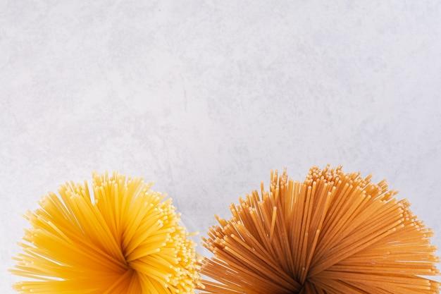 Ruwe gele en bruine spaghetti op witte ondergrond