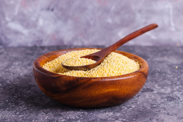 Ruwe gele gierst voor goede voeding en gezondheid in een houten plaat op een grijze achtergrond