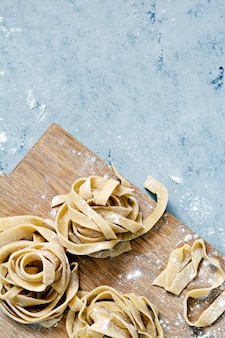 Ruwe gele zelfgemaakte italiaanse pasta pappardelle, fettuccine of tagliatelle op een blauwe achtergrond