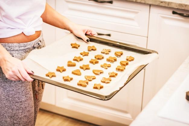 Ruwe gemberkoekjes op bakselblad in vrouwenhanden