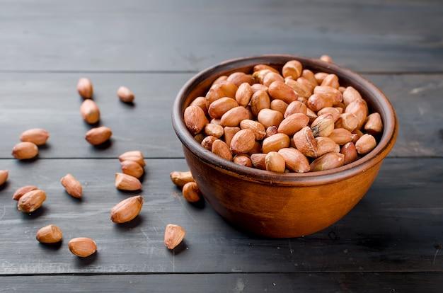 Ruwe gepelde pinda's in een keramische kom
