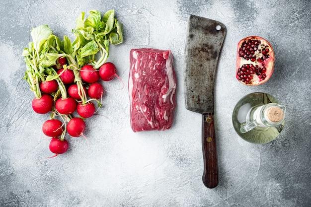 Ruwe geplaatste carpaccio-ingrediënten, op grijze steen