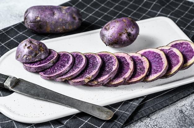 Ruwe gesneden purpere aardappels op een wit hakbord.