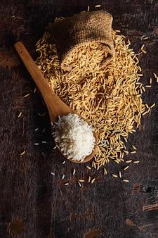 Ruwe gestoomde rijst en padie op houten achtergrond