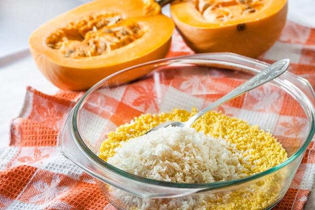 Ruwe gewassen gierst en rijst in een glaspan tijdens het koken van de pompoenhavermoutpap van de melk met rozijnen
