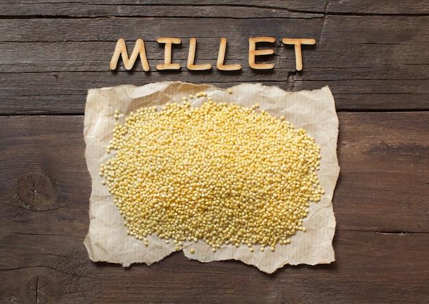 Ruwe gierst met een bovenaanzicht van het woord millet op een houten tafel