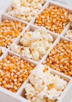 Ruwe gouden suikermaïszaden en popcorn in witte houten doos op lichte achtergrond macro