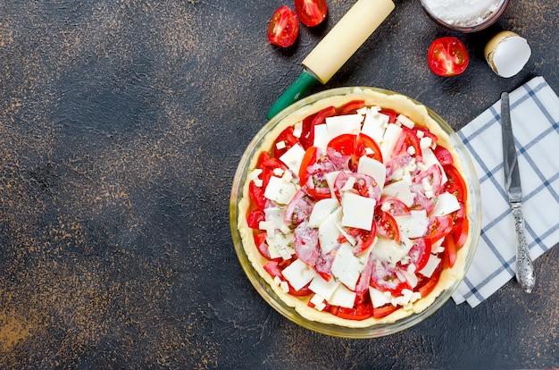 Ruwe griekse taart met feta en tomaten voor het bakken