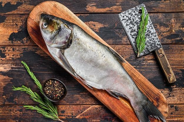Ruwe hele vis zilveren karper op een snijplank met rozemarijn. donker.