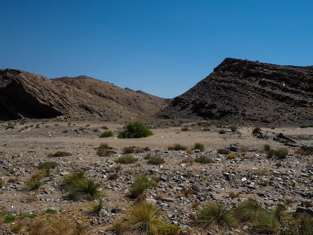 Ruwe het landschapsgrond van de rotsberg van namib-woestijn unieke aardrijkskunde en duidelijke blauwe hemel