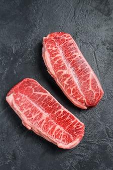 Ruwe hoogste bladlapje vlees dry-aged op zwarte. bovenaanzicht