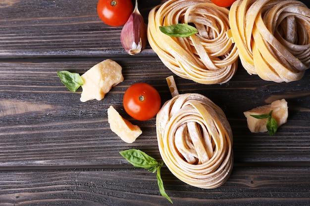 Ruwe huisgemaakte deegwaren met kaas en groenten op houten lijst