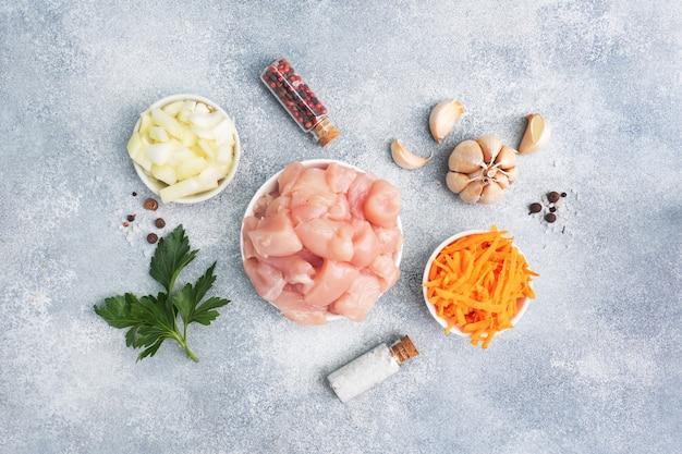 Ruwe ingrediënten voor het koken van een gebraad. kipfilet, geraspte wortelen en gehakte ui knoflook met kruiden en specerijen. grijs, kopieer ruimte, bovenaanzicht.