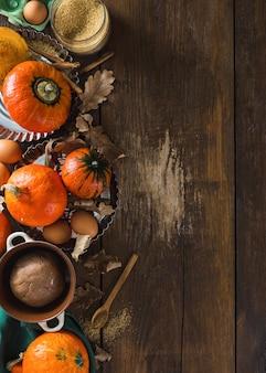Ruwe ingrediënten voor het koken van pompoen taart met droge herfst bladeren op houten achtergrond met kopie ruimte