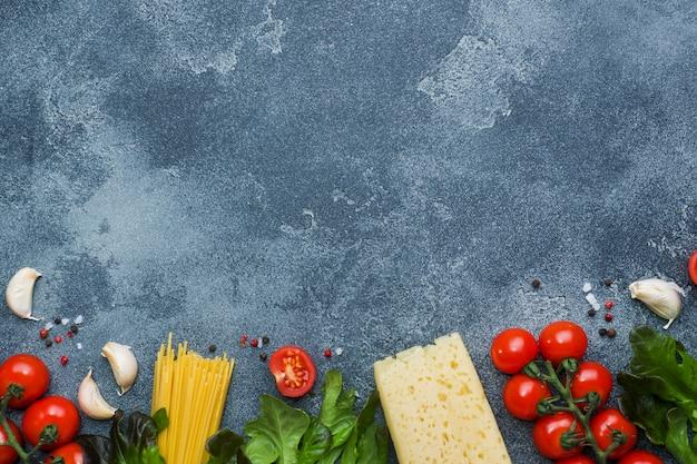 Ruwe italiaanse deegwarenspaghetti en kokende ingrediënten kersentomaten kaasgreens. italiaans voedsel donkere stenen oppervlak. bovenaanzicht met kopie ruimte