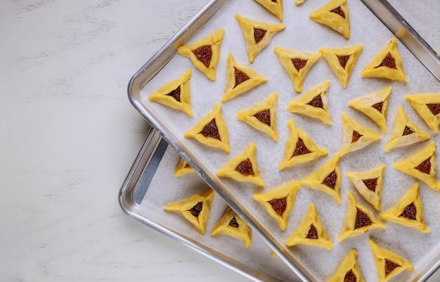 Ruwe joodse koekjes met jam op ovenschaal.