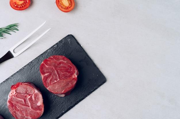 Ruwe kalfsmedaillons op zwarte stenen bord close-up