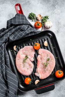Ruwe kalkoen steaks in een zwarte pan
