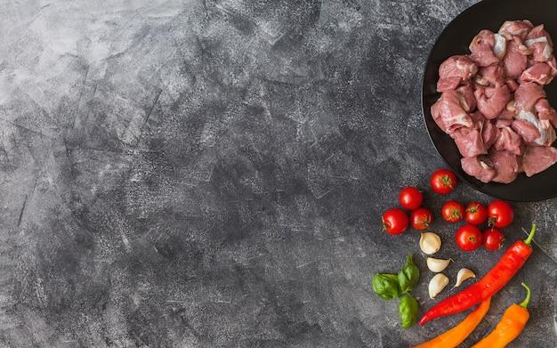 Ruwe kippen met ingrediënten op zwarte textuurachtergrond